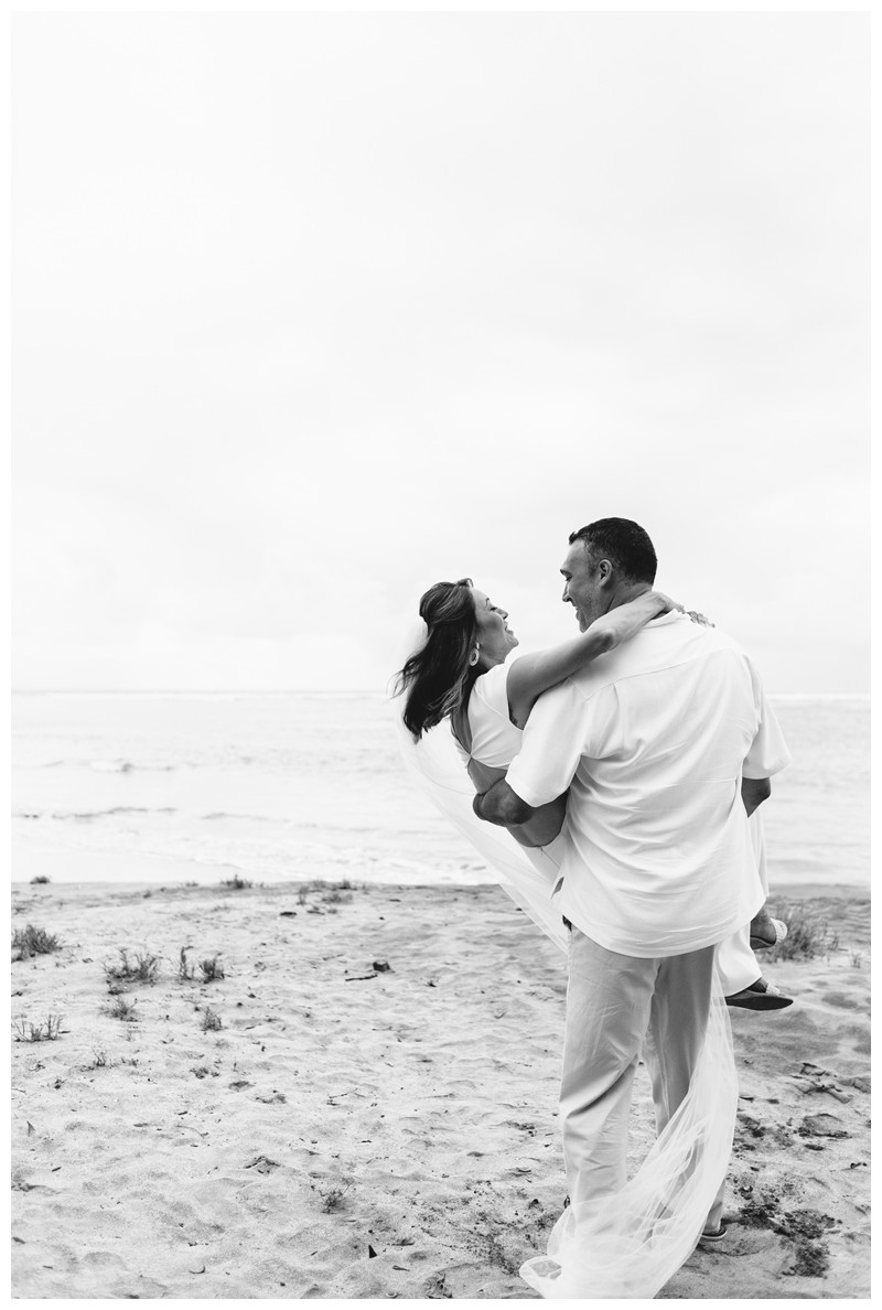 Husband carrying his wife on the beach. Elopement on the Beach in Tamarindo Costa Rica. Photographed by Kristen M. Brown, Samba to the Sea Photography.