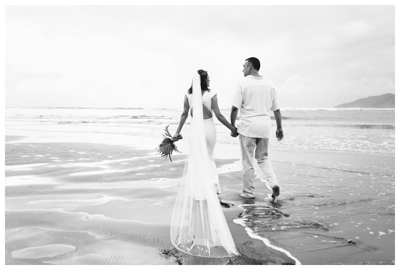 Husband and wife walking on the beach. Elopement on the Beach in Tamarindo Costa Rica. Photographed by Kristen M. Brown, Samba to the Sea Photography.