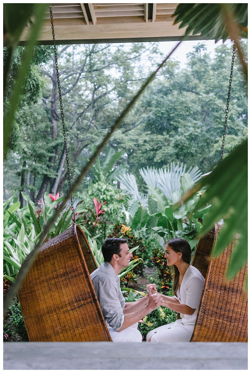 Couple swinging in hanging egg chairs during engagement Photos in Nosara Costa Rica at The Guilded Iguana. Photographed by Kristen M. Brown, Samba to the Sea Photography.