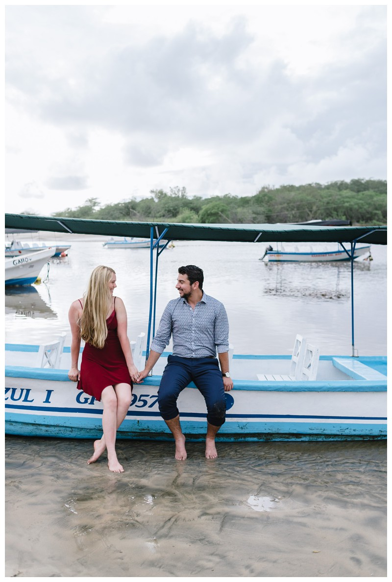 Couple sitting on a Panga boat in Costa Rica. Surprise beach proposal in Tamarindo Costa Rica. Photographed by Kristen M. Brown, Samba to the Sea Photography.