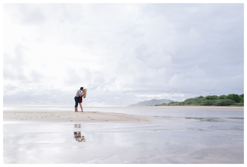 Couple kissing on the beach in Costa Rica. Surprise beach proposal in Tamarindo Costa Rica. Photographed by Kristen M. Brown, Samba to the Sea Photography.