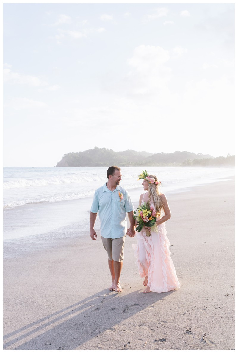 Husband and wife walking on the beach after their vow renewal in Samara Costa Rica. Photographed by Kristen M. Brown, Samba to the Sea Photography.