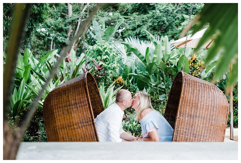 Mom and dad kissing in hanging eggs chairs during family photos in Nosara Costa Rica at The Guilded Iguana. Photographed by Kristen M. Brown, Samba to the Sea Photography.