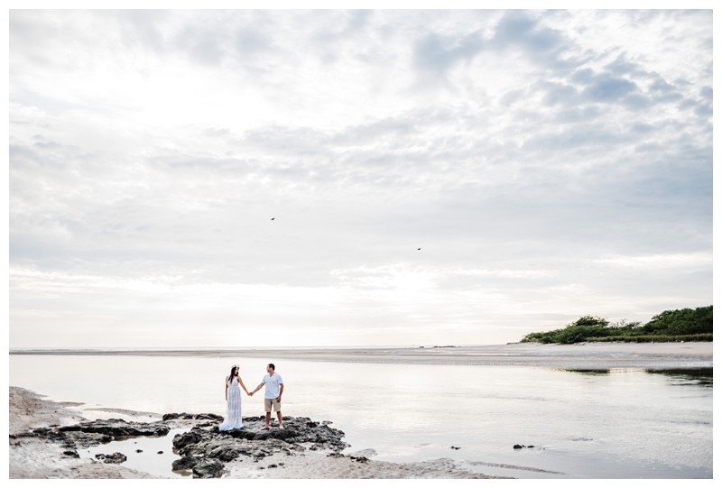 Couple holding hands on the beach during their honeymoon photos in Tamarindo Costa Rica. Photographed by Kristen M. Brown, Samba to the Sea Photography.