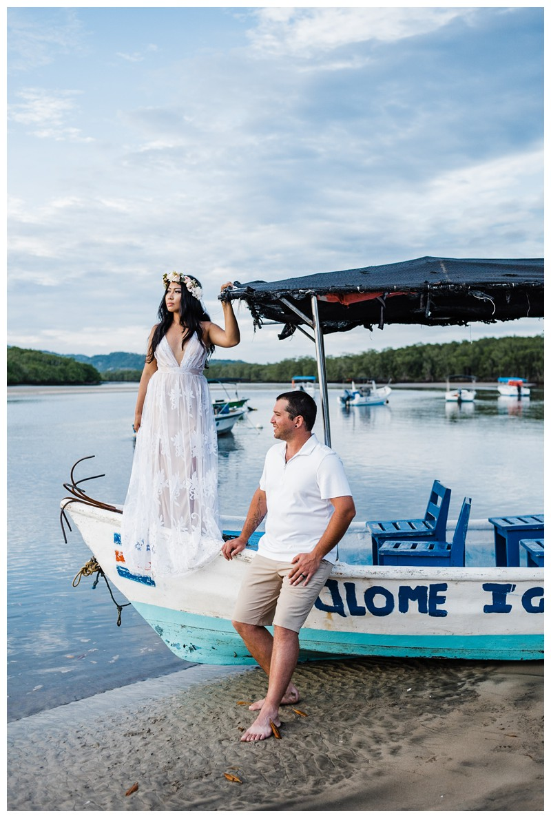 Romantic boho portrait of couple on the beach on a panga boat in the Tamarindo estuary. Beach honeymoon photos in Tamarindo Costa Rica. Photographed by Kristen M. Brown, Samba to the Sea Photography.