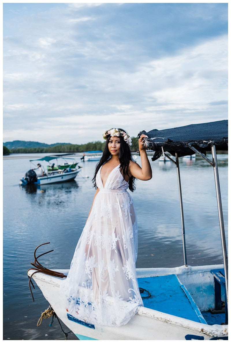 Romantic boho portrait of bride on the beach on a panga boat in the Tamarindo estuary. Beach honeymoon photos in Tamarindo Costa Rica. Photographed by Kristen M. Brown, Samba to the Sea Photography.