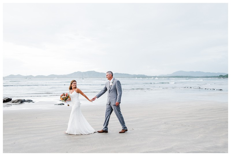 Bride and groom walking on the beach. Sunset elopement in Tamarindo Costa Rica. Photographed by Kristen M. Brown, Samba to the Sea Photography.