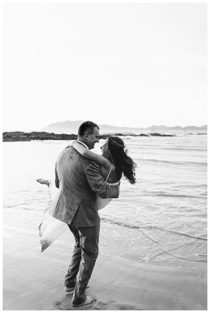 Groom carrying his bride on the beach. Sunset elopement in Tamarindo Costa Rica. Photographed by Kristen M. Brown, Samba to the Sea Photography.