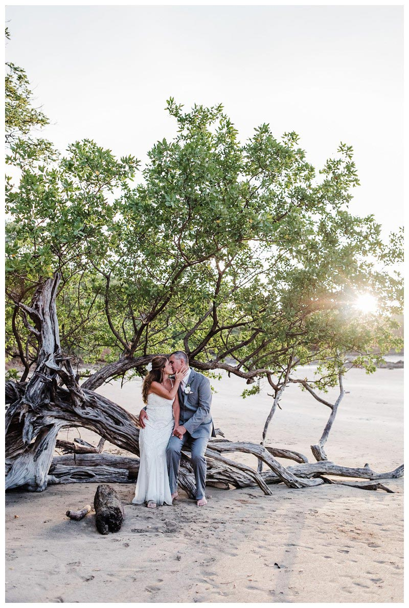 Bride and groom kissing under a driftwood tree on the beach. Sunset elopement in Tamarindo Costa Rica. Photographed by Kristen M. Brown, Samba to the Sea Photography.