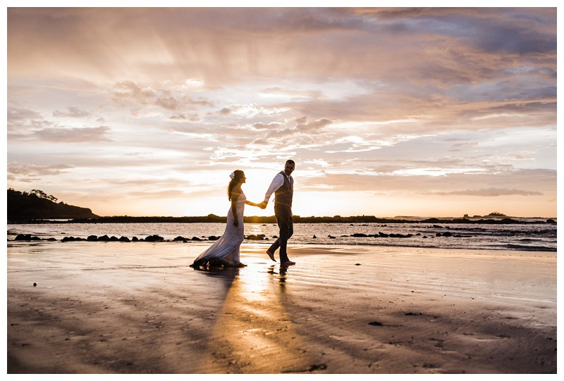Bride and groom walking on the beach during sunset. Sunset elopement in Tamarindo Costa Rica. Photographed by Kristen M. Brown, Samba to the Sea Photography.