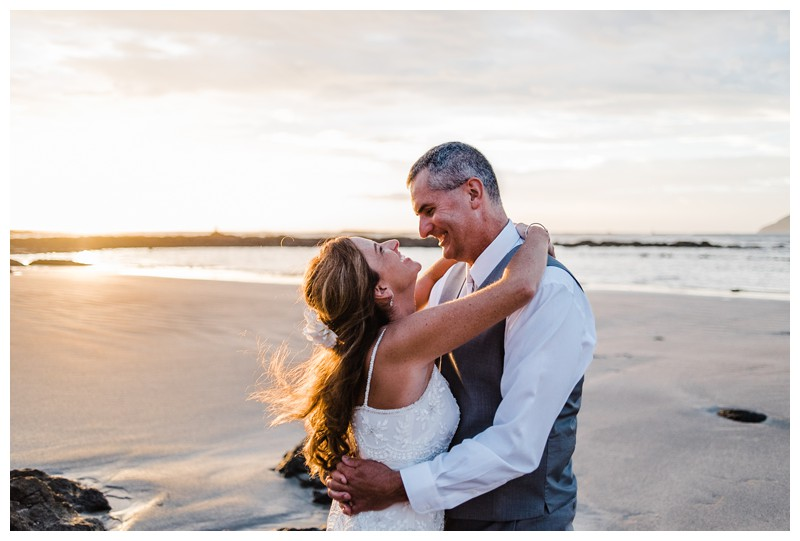 Bride and groom laughing on the beach. Sunset elopement in Tamarindo Costa Rica. Photographed by Kristen M. Brown, Samba to the Sea Photography.