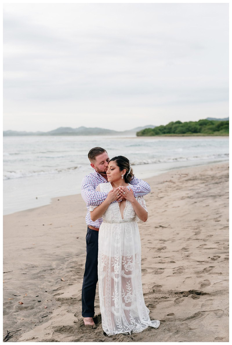 Bride and groom embracing on the beach during sunset in Costa Rica. Beach Elopement in Playa Tamarindo, Costa Rica. Photographed by Kristen M. Brown, Samba to the Sea Photography.