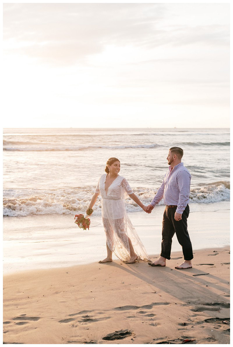 Bride and groom walking on the beach during sunset in Costa Rica. Beach Elopement in Playa Tamarindo, Costa Rica. Photographed by Kristen M. Brown, Samba to the Sea Photography.
