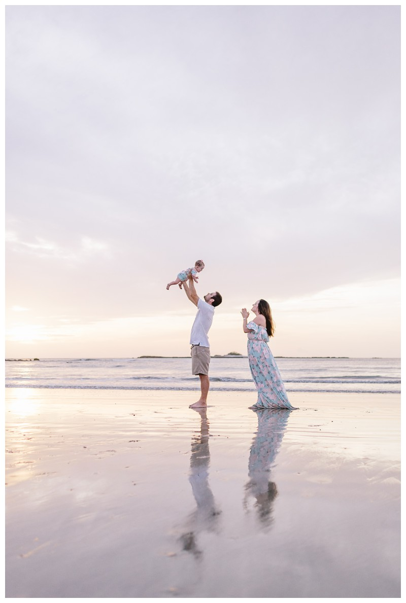 Dad throwing his baby girl in the air during beach family photos in Guanacaste Costa Rica. Photographed by Kristen M. Brown, Samba to the Sea Photography. Beach lifestyle photos in Costa Rica. Photographed by Kristen M. Brown, Samba to the Sea Photography.