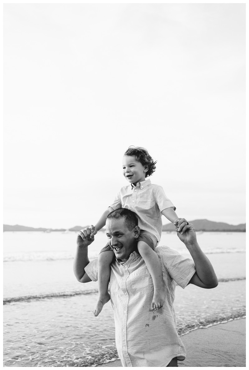 Dad giving his son a piggy back ride on the beach. Tamarindo Costa Rica beach family photos. Photographed by Kristen M. Brown, Samba to the Sea Photography. Beach lifestyle photos in Costa Rica. Photographed by Kristen M. Brown, Samba to the Sea Photography.