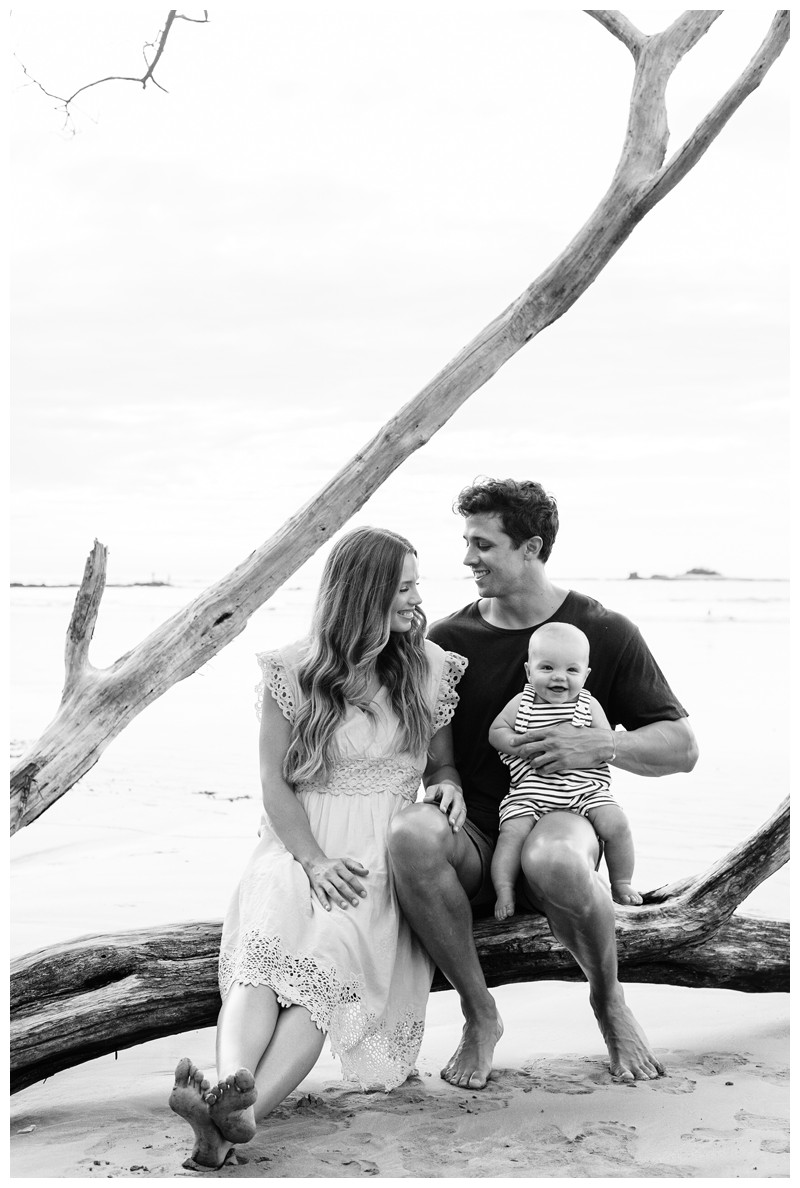Young family sitting on a beautiful driftwood tree. Tamarindo family photos. Photographed by Kristen M. Brown, Samba to the Sea Photography.
