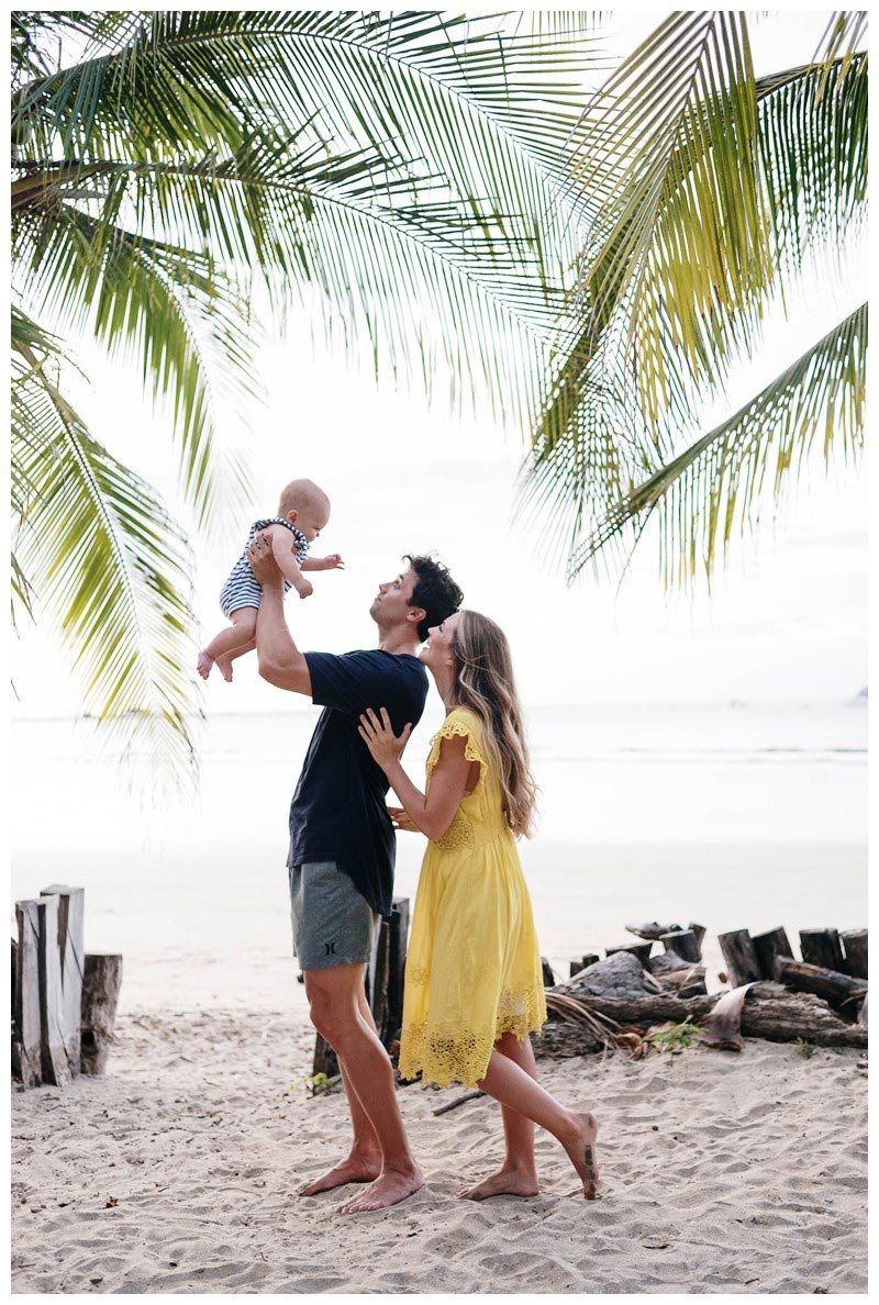 Dad holding his little boy in the air with mom looking under beautiful palm trees. Tamarindo family photos. Photographed by Kristen M. Brown, Samba to the Sea Photography.