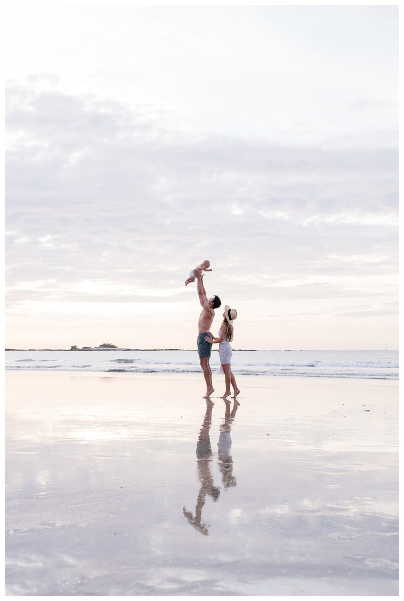 Dad throwing his little boy in the air with mom looking on the beach in Costa Rica. Tamarindo family photos. Photographed by Kristen M. Brown, Samba to the Sea Photography.