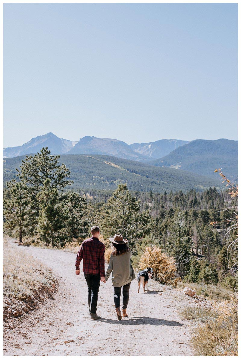 Couple holding hands walking with their dog. Fall couple's photos in Rocky Mountain National Park Colorado. Photographed by Kristen M. Brown, Samba to the Sea Photography.