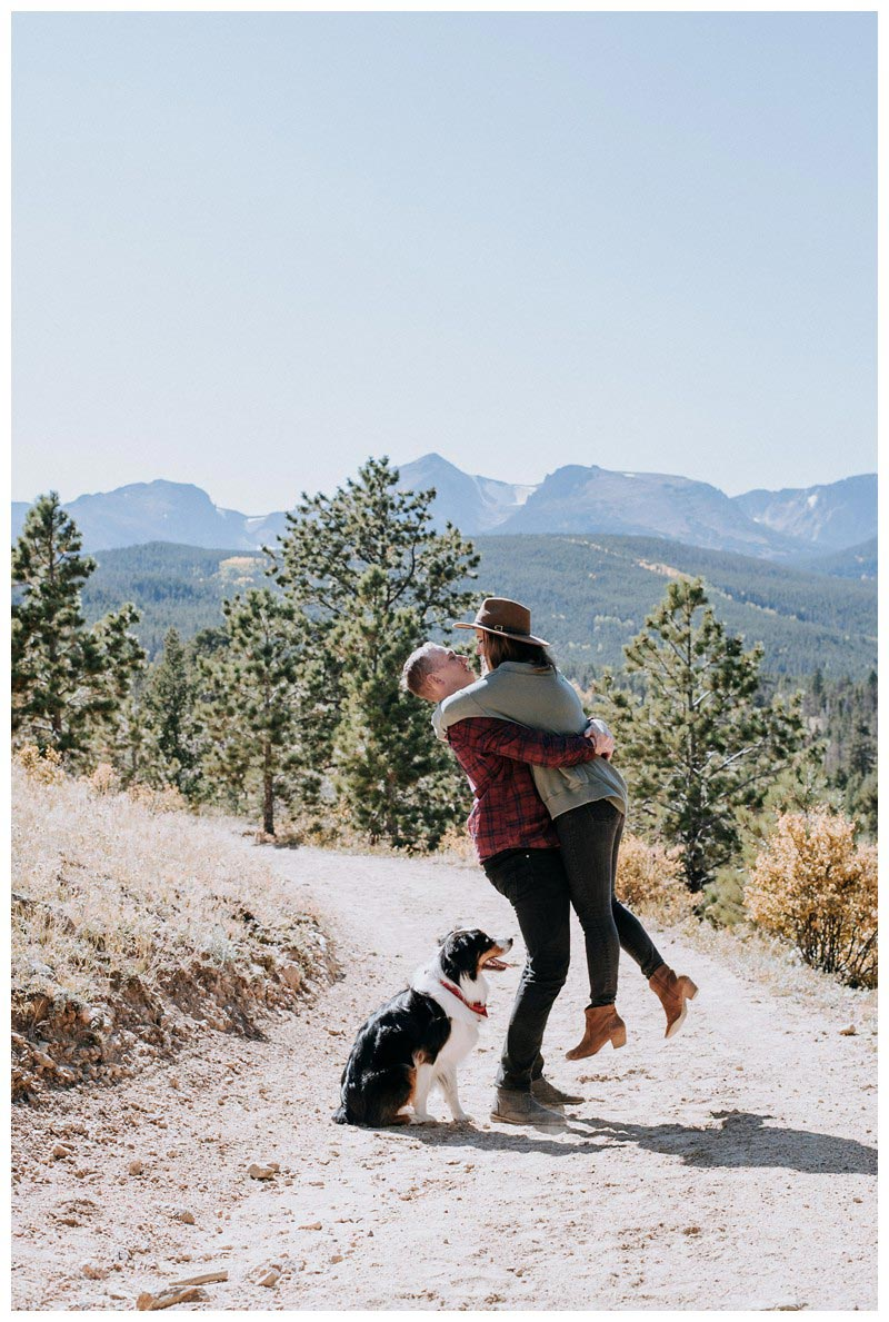 Husband holding his wife with beautiful mountain background. Fall couple's photos in Rocky Mountain National Park Colorado. Photographed by Kristen M. Brown, Samba to the Sea Photography.