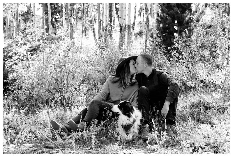 Couple kissing under a golden Aspen grove with their dog. Fall couple's photos in Rocky Mountain National Park Colorado. Photographed by Kristen M. Brown, Samba to the Sea Photography.