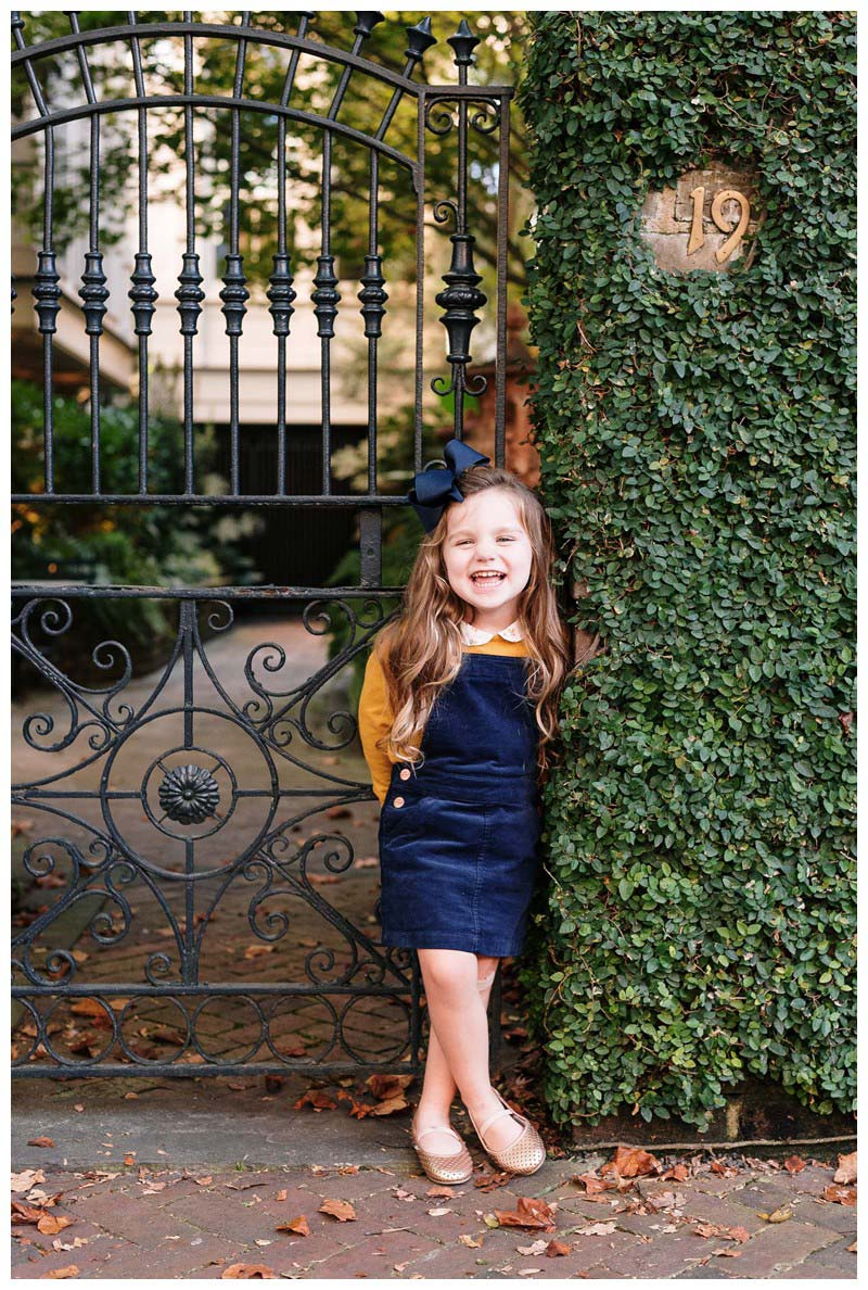 Little girl laughing in front of an iron door in Savannah, Georgia. Family photos in downtown Savannah Georgia. Photographed by Kristen M. Brown, Samba to the Sea Photography.