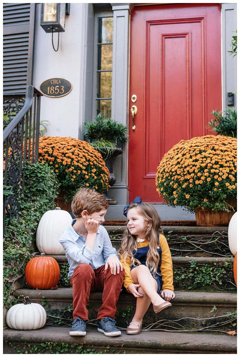 Brother and sister sitting on a historic front stoop with fall mums and pumpkins in Savannah, Georgia. Family photos in downtown Savannah Georgia. Photographed by Kristen M. Brown, Samba to the Sea Photography.