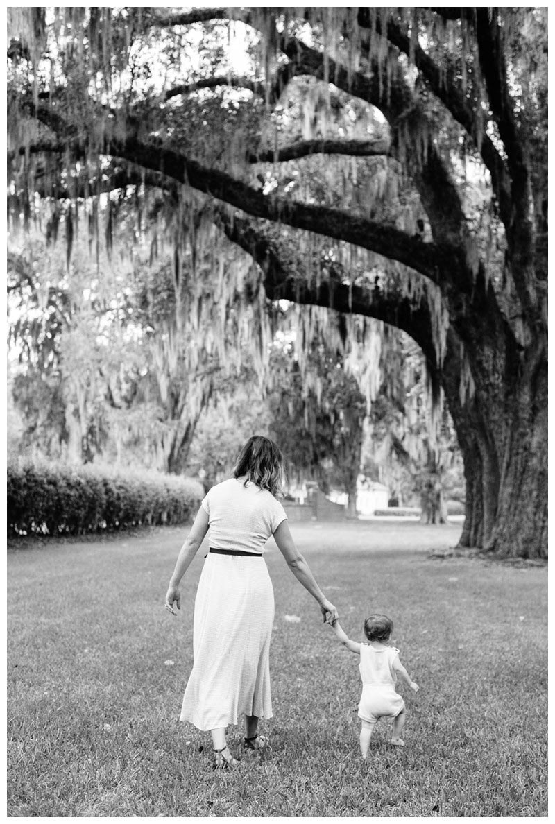 Mom and young daughter walking under Oak trees. Ford Plantation Family Photos in Savannah, Georgia. Photographed by Kristen M. Brown, Samba to the Sea Photography.