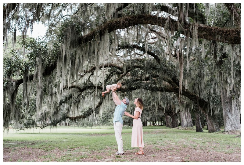 Dad throwing his little girl in the air under a majestic Oak tree. Ford Plantation Family Photos in Savannah, Georgia. Photographed by Kristen M. Brown, Samba to the Sea Photography.