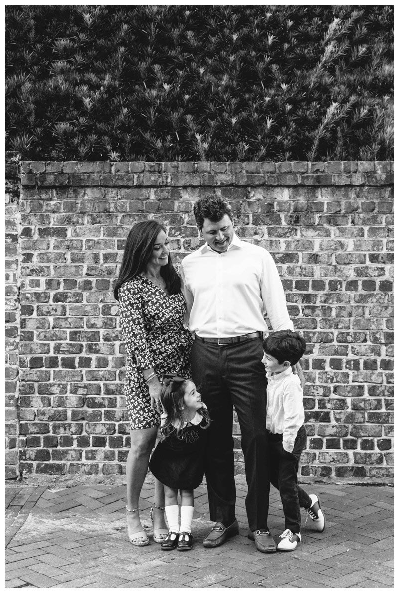 Family portrait in front of a brick wall in downtown Savannah, Georgia. Holiday family photos in downtown Savannah Georgia. Photographed by Kristen M. Brown, Samba to the Sea Photography.