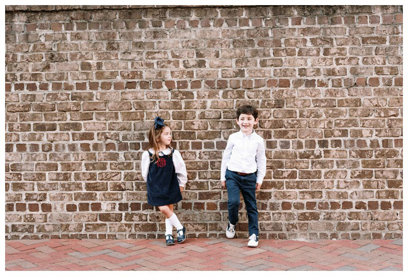 Brother and sister standing in front of a brick wall in downtown Savannah, Georgia. Holiday family photos in downtown Savannah Georgia. Photographed by Kristen M. Brown, Samba to the Sea Photography.
