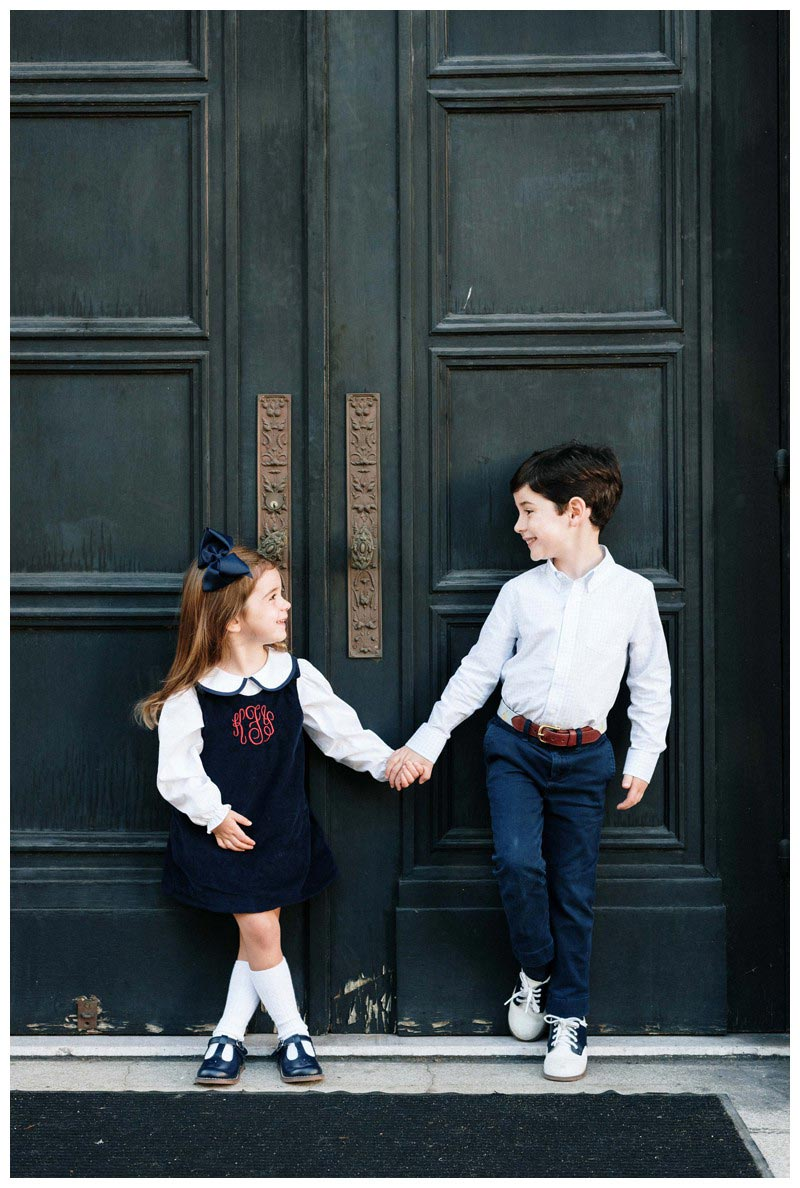 Brother and sister holding hands in front of the doors at First Baptist Church of Savannah, Georgia in Chippewa Square. Holiday family photos in downtown Savannah Georgia. Photographed by Kristen M. Brown, Samba to the Sea Photography.