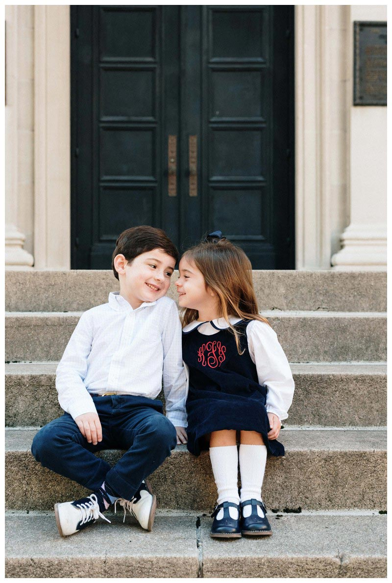 Brother and sister sitting on steps front of the doors at First Baptist Church of Savannah, Georgia in Chippewa Square. Holiday family photos in downtown Savannah Georgia. Photographed by Kristen M. Brown, Samba to the Sea Photography.