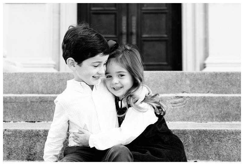Sister hugging her brother sitting on steps front of the doors at First Baptist Church of Savannah, Georgia in Chippewa Square. Holiday family photos in downtown Savannah Georgia. Photographed by Kristen M. Brown, Samba to the Sea Photography.