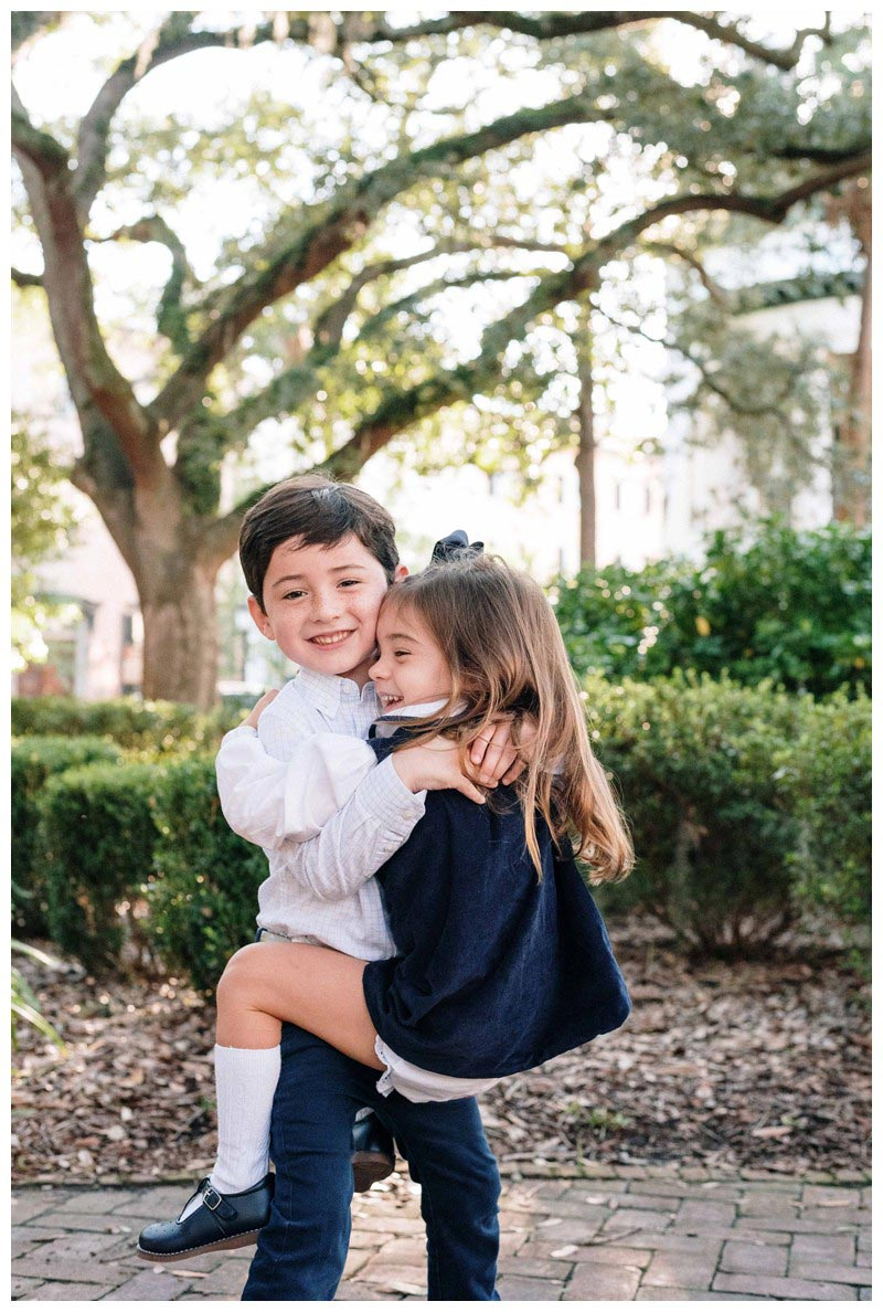 Brother giving his sister a hug in Chippewa Square in Savannah, Georgia. Holiday family photos in downtown Savannah Georgia. Photographed by Kristen M. Brown, Samba to the Sea Photography.