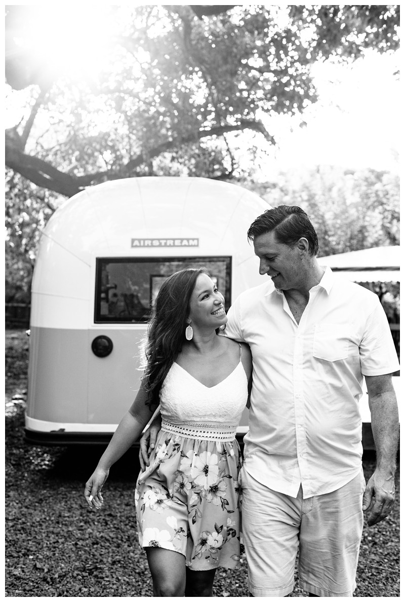 Couple walking in front of a turquoise and white airstream in Nosara. Engagement photos in Playa Guiones Costa Rica. Photographed by Kristen M. Brown, Samba to the Sea Photography.