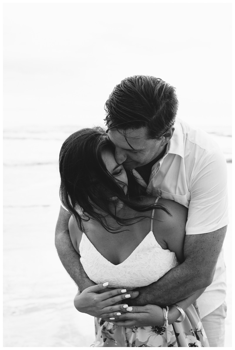 Fiance embracing his girlfriend on the beach in Nosara. Engagement photos in Playa Guiones Costa Rica. Photographed by Kristen M. Brown, Samba to the Sea Photography.