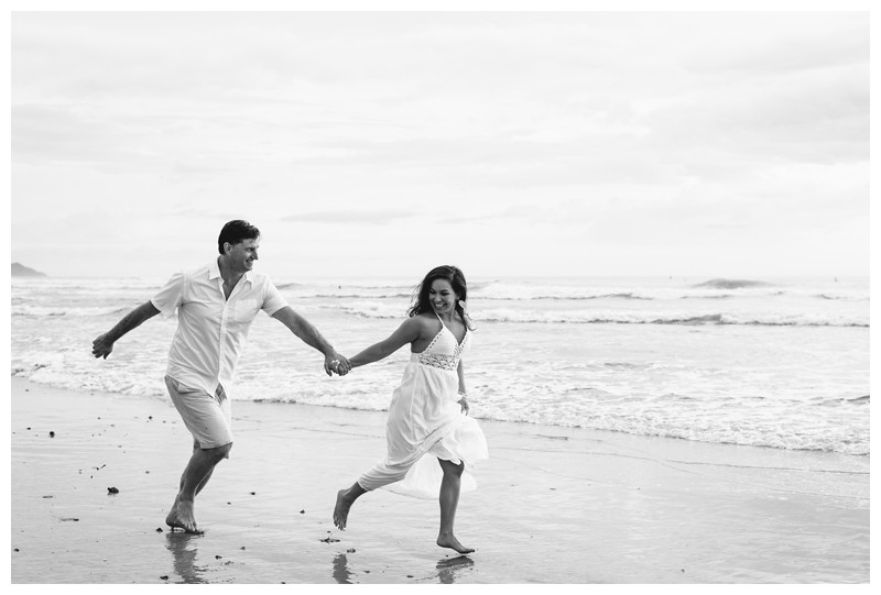 Couple running on the beach in Nosara. Engagement photos in Playa Guiones Costa Rica. Photographed by Kristen M. Brown, Samba to the Sea Photography.