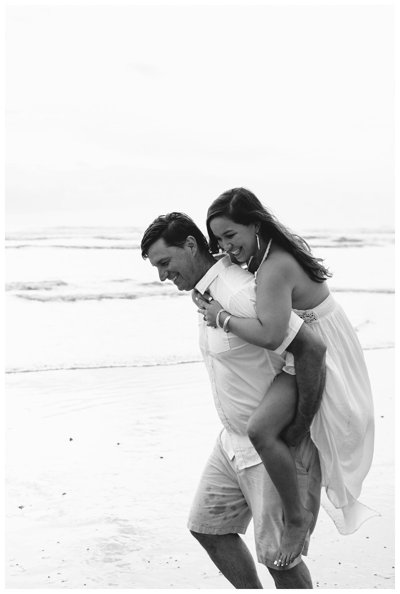Fiance giving his girlfriend a piggyback ride on the beach in Nosara. Engagement photos in Playa Guiones Costa Rica. Photographed by Kristen M. Brown, Samba to the Sea Photography.