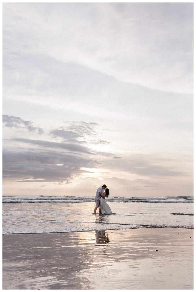Couple kissing on the beach during sunset in Nosara. Engagement photos in Playa Guiones Costa Rica. Photographed by Kristen M. Brown, Samba to the Sea Photography.