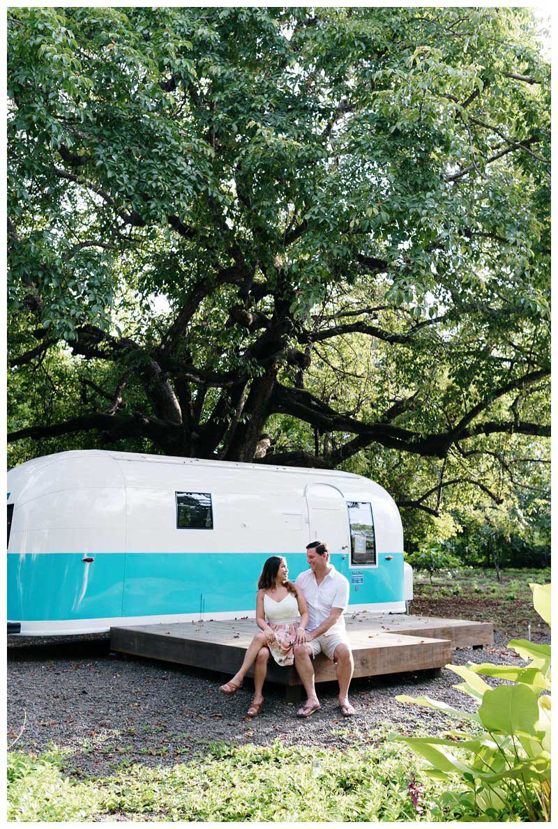Couple sitting in front of a turquoise and white airstream in Nosara. Engagement photos in Playa Guiones Costa Rica. Photographed by Kristen M. Brown, Samba to the Sea Photography.