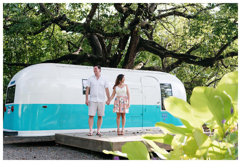 Couple standing in front of a turquoise and white airstream in Nosara. Engagement photos in Playa Guiones Costa Rica. Photographed by Kristen M. Brown, Samba to the Sea Photography.