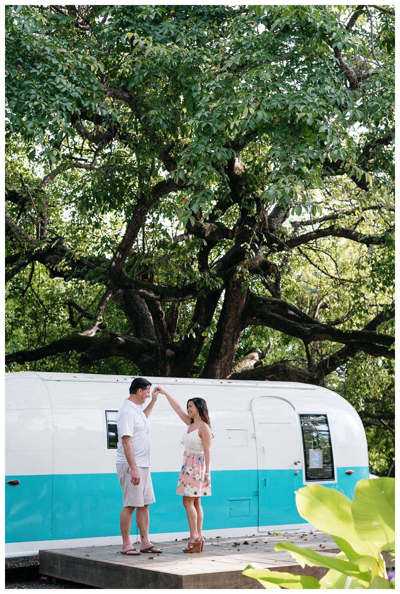 Couple dancing in front of a turquoise and white airstream in Nosara. Engagement photos in Playa Guiones Costa Rica. Photographed by Kristen M. Brown, Samba to the Sea Photography.