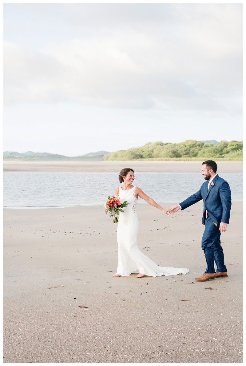 Bride and groom walking on the beach during sunset. Tamarindo wedding at Casa Compass in Costa Rica. Photographed by Kristen M. Brown, Samba to the Sea Photography.