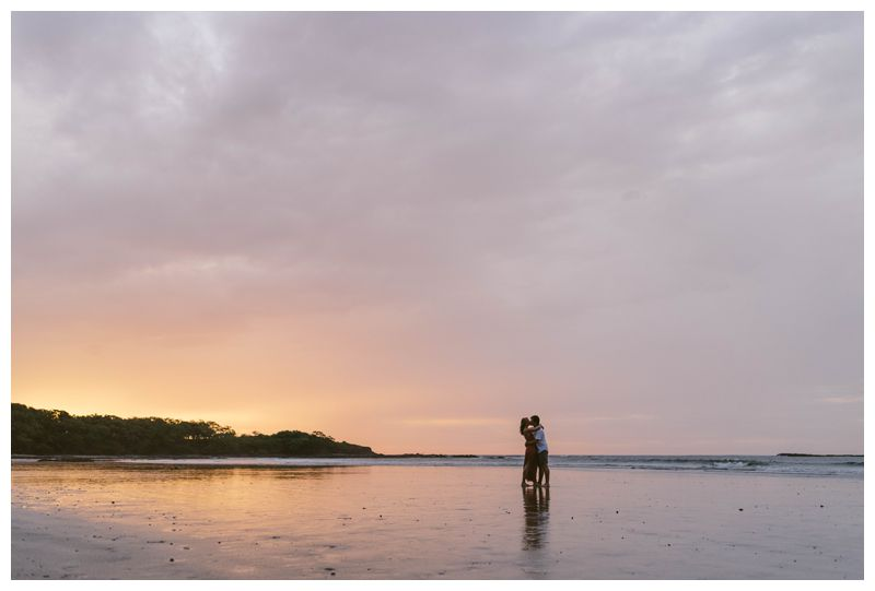 Husband and wife kissing on the beach in Tamarindo during a pastel pink sunkset. Beach anniversary photos in Costa Rica. Photographed by Kristen M. Brown, Samba to the Sea Photography.
