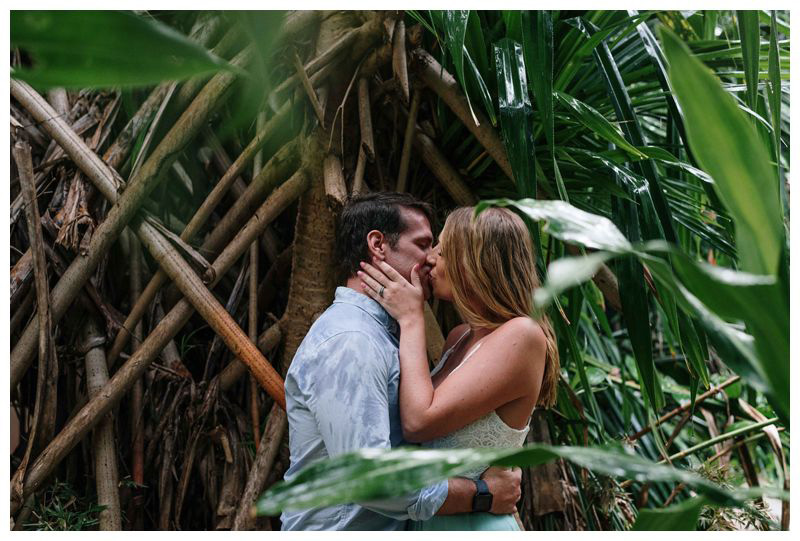 Husband and wife kissing in a jungle garden at Hotel Capitan Suizo in Tamarindo. Beach anniversary photos in Costa Rica. Photographed by Kristen M. Brown, Samba to the Sea Photography.