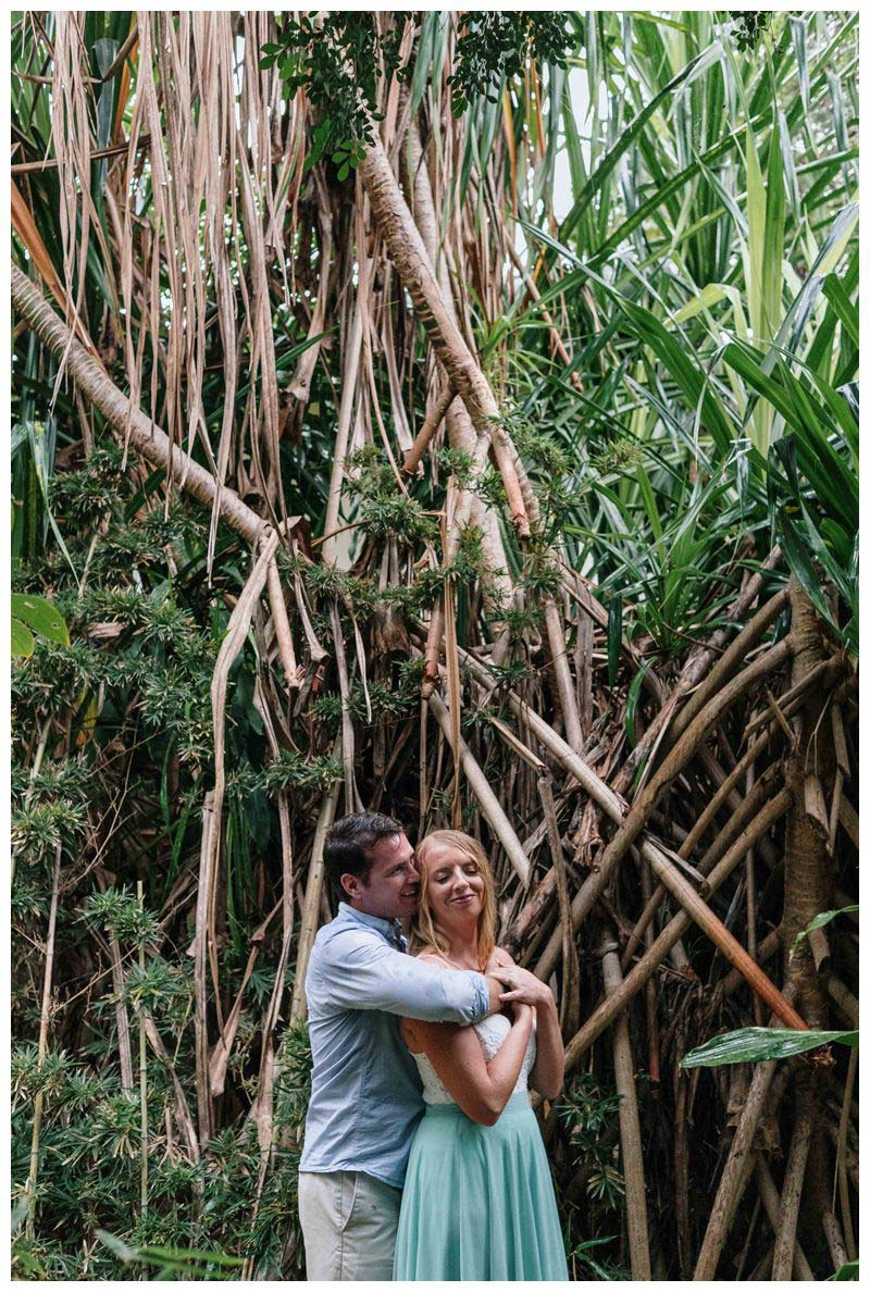 Husband and wife embracing in a jungle garden at Hotel Capitan Suizo in Tamarindo. Beach anniversary photos in Costa Rica. Photographed by Kristen M. Brown, Samba to the Sea Photography.