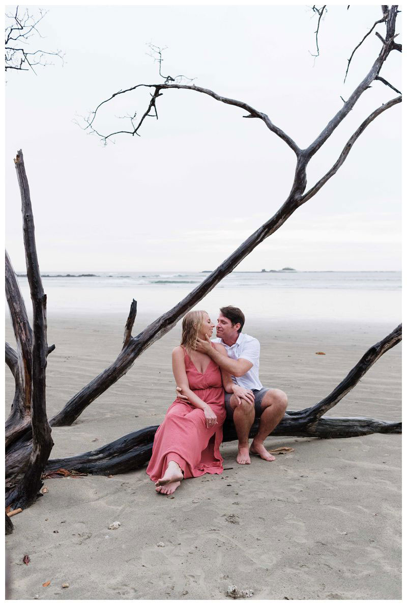 Husband and wife sitting on a driftwood tree kissing on the beach in Tamarindo. Beach anniversary photos in Costa Rica. Photographed by Kristen M. Brown, Samba to the Sea Photography.