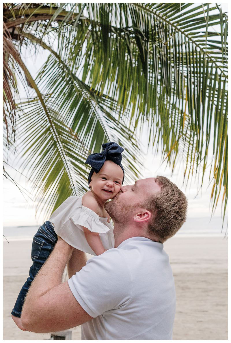 Baby girl smiling as dad kisses her cheek. Beach family photos in Tamarindo Costa Rica. Photographed by Kristen M. Brown, Samba to the Sea Photography.