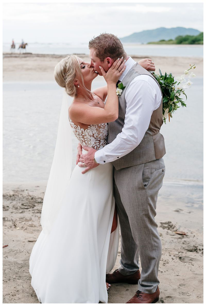 Bride and groom kissing on the beach. Destination tropical wedding in Tamarindo, Costa Rica. Photographed by Kristen M. Brown, Samba to the Sea Photography.